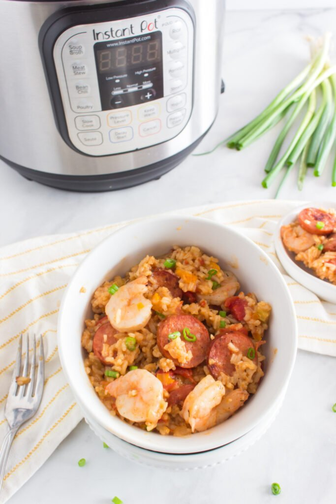 Jambalaya in a white bowl with pressure cooker in background
