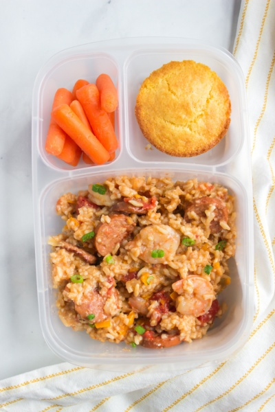 Jambalaya packed in a lunchbox with a muffin and baby carrots