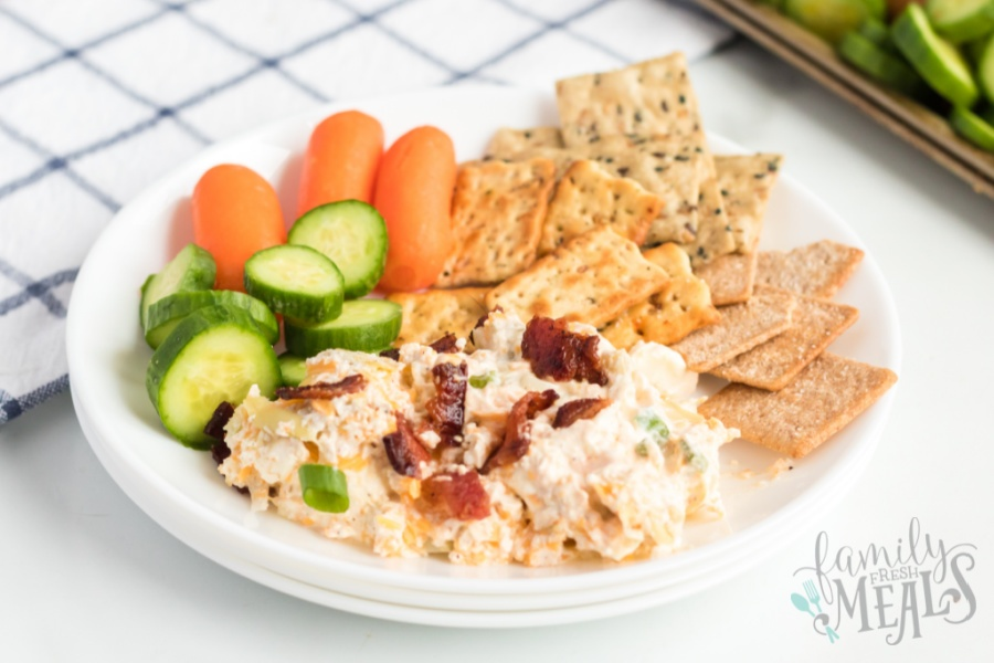 Mississippi Sin dip on a plate with vegetables and crackers