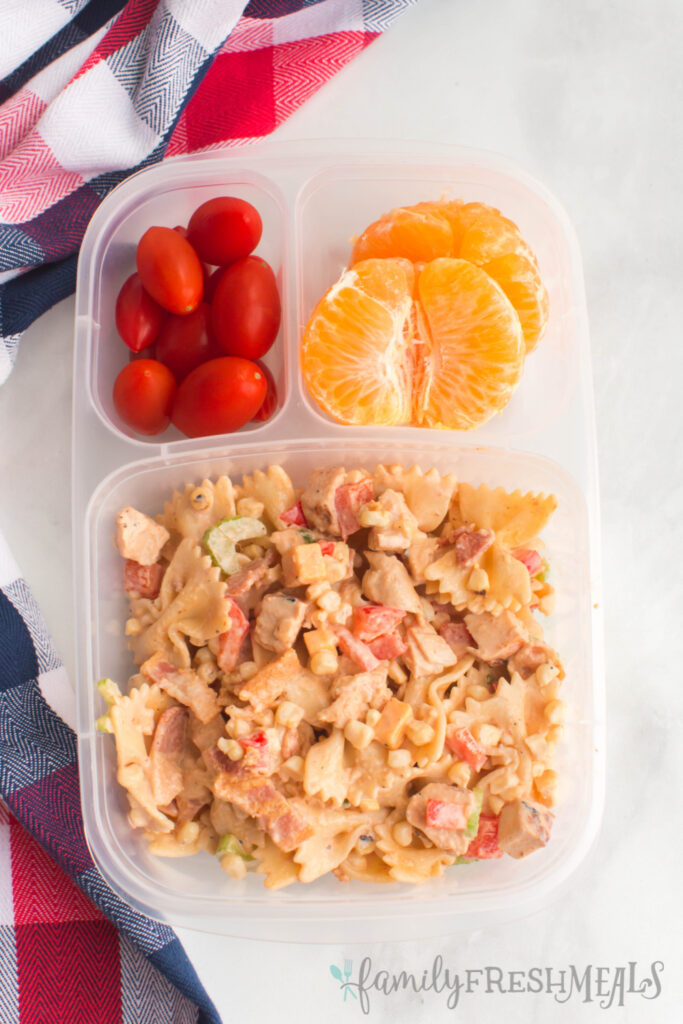 bbq chicken pasta salad packed in a lunchbox with orange slices and cherry tomatoes
