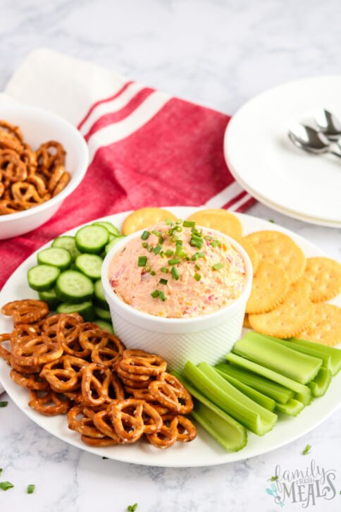 Pimento Cheese Spread recipe in a bowl with pretzels, cracker, celery and cucumbers