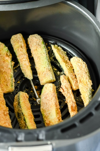 uncooked zucchini fries in air fryer basket