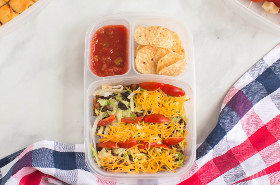 taco salad and chips and salsa in a lunchbox