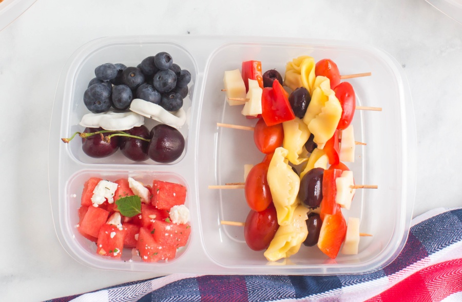 pasta salad skewers, and fruit packed in a lunchbox