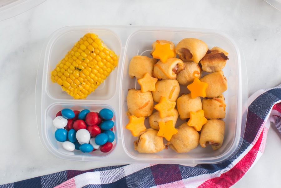 mini hotdogs, cheese stars, candies and corn on the cob in a lunchbox