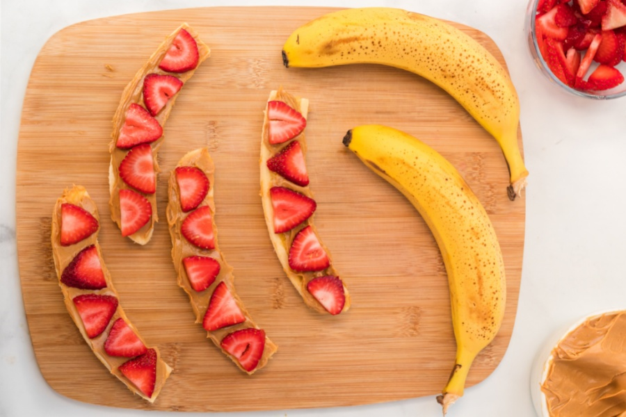 sliced bananas with nut butter on slice strawberries