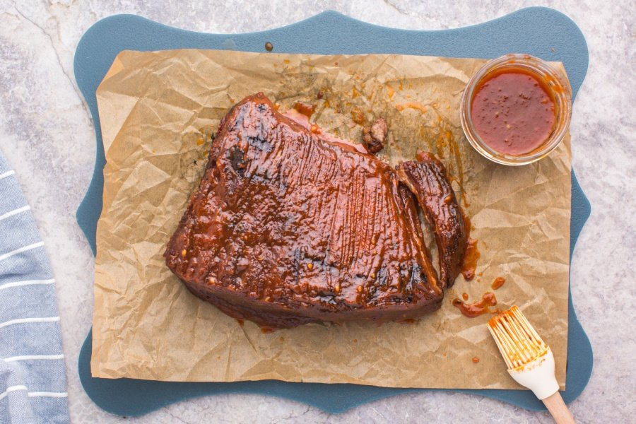 BBQ Brisket on parchment paper with a small up of bbq sauce