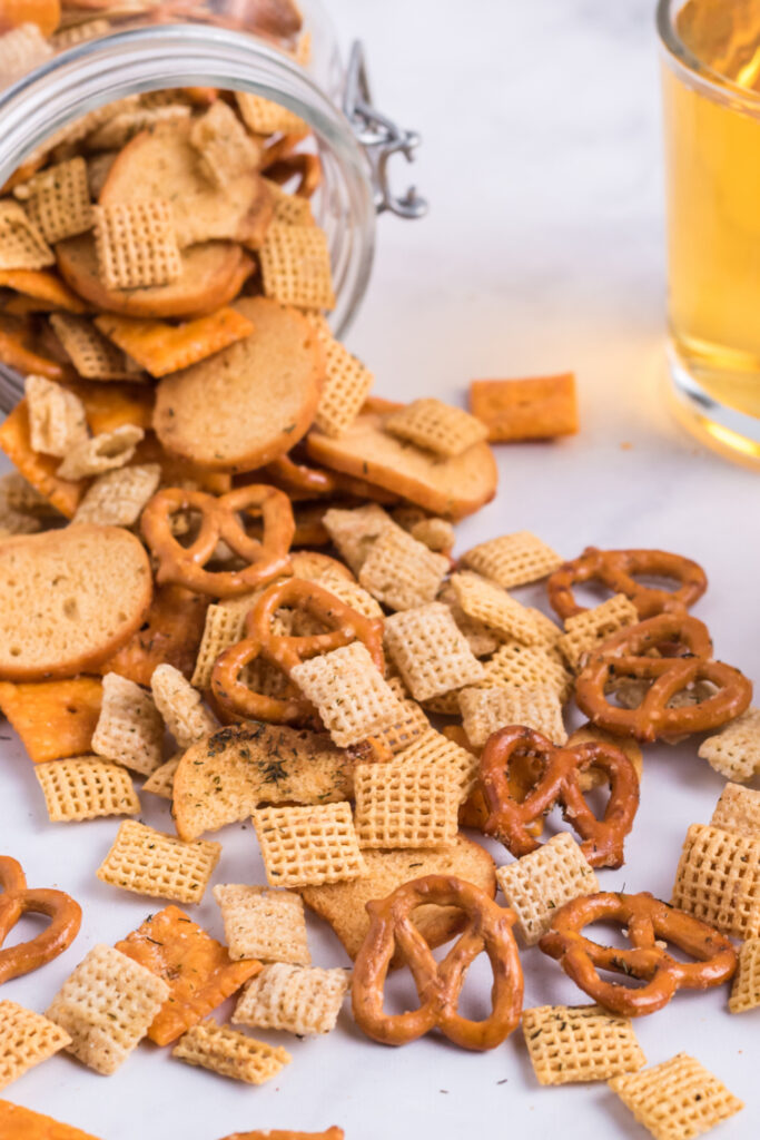 Dill Pickle Chex Mix pouring out of glass jar