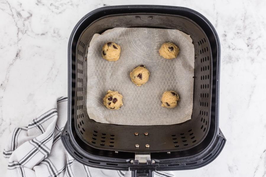 5 cookie dough balls in an air fryer basket