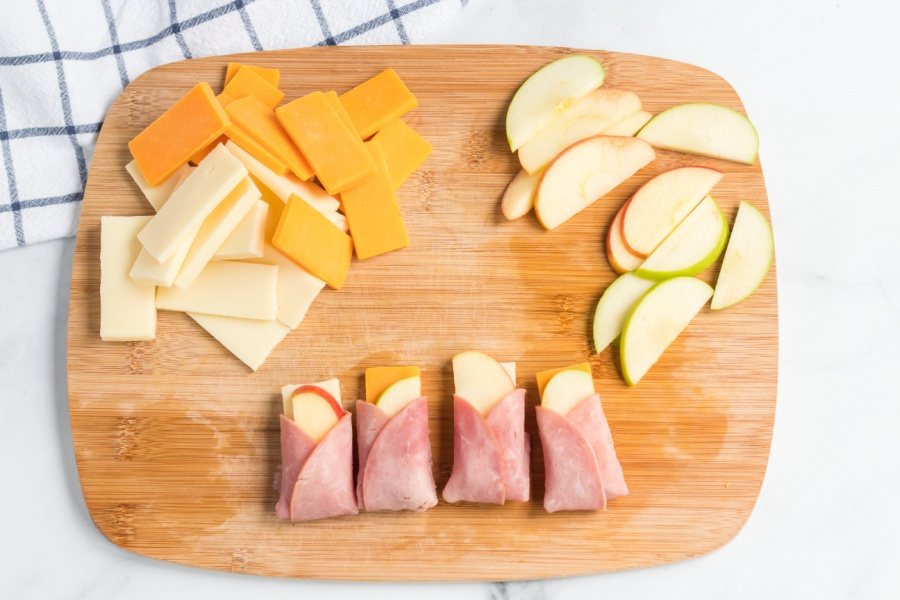 ham apple cheese wraps on a cutting board