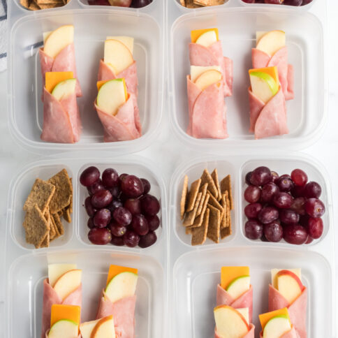 4 lunchboxes with ham apple cheese wraps in them