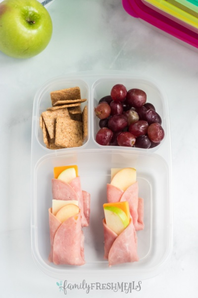 ham apple cheese wraps in a lunchbox with crackers and grapes