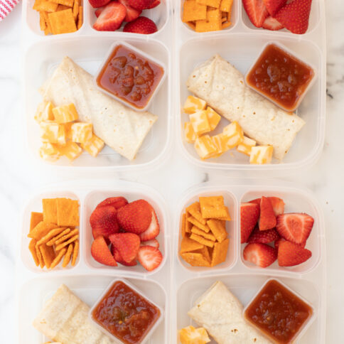 4 lunchboxes packed with burritos, strawberries, crackers, cheese and salsa-5