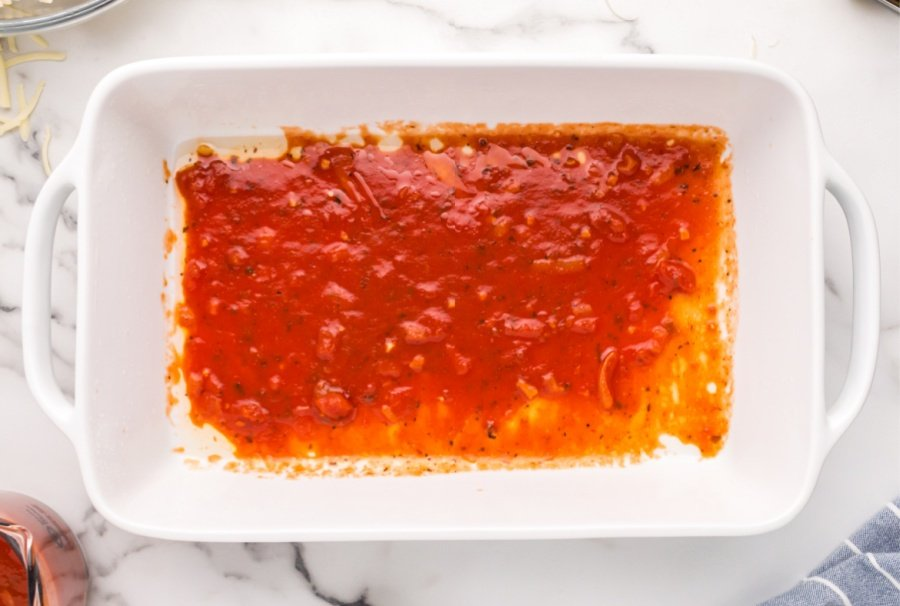 marinara sauce spread into baking dish