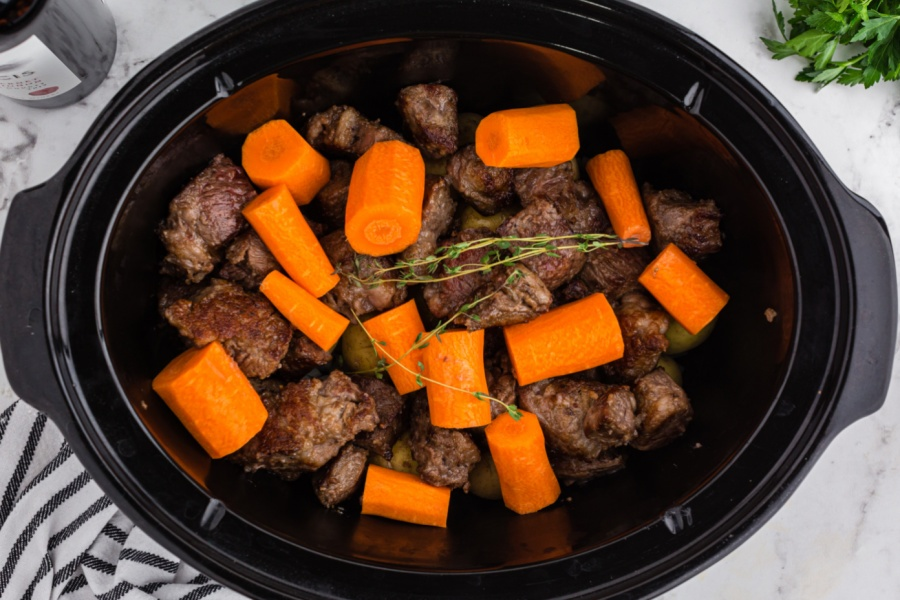 meat and veggies placed in slow cooker