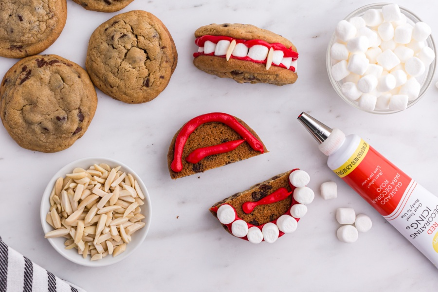 showing how to put marshmallow teeth and icing on cookie